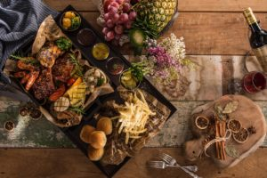 food: a very artsy food platter on wooden table with grilled vegetables, fries, fruit and cinnamon